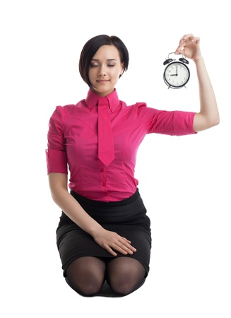 young woman in business suit sit in yoga pose with clock isolated photo