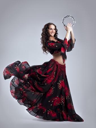 Jonge schoonheid vrouw dansen in zigeuner kostuum met tamboerijn geïsoleerde Stockfoto