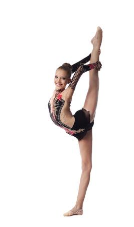 acrobacia: Niña gimnasta profesional se encuentra en una hermosa divide - mira a la cámara aislada