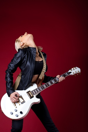 Sexy rock woman in black leather play with passion on electro guitar on red background photo