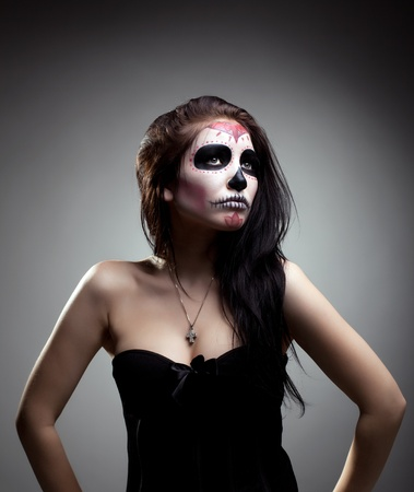 dia de los muertos: Serious woman in day of the dead mask skull face art look aside Stock Photo