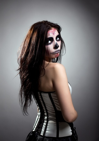 Serious woman in day of the dead mask skull face art look aside photo