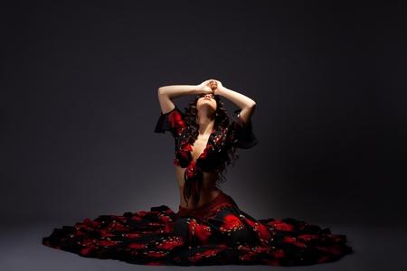 danseuse flamenco: jeune femme mignonne s'asseoir dans gitane noire et rouge - dramatique pose