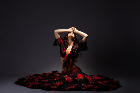 flamenco dancer: mujer joven linda gitana sentarse en negro y rojo - espectacular posando