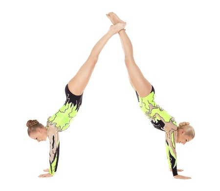 acrobat gymnast: Two young acrobats woman stand on hands isolated Stock Photo