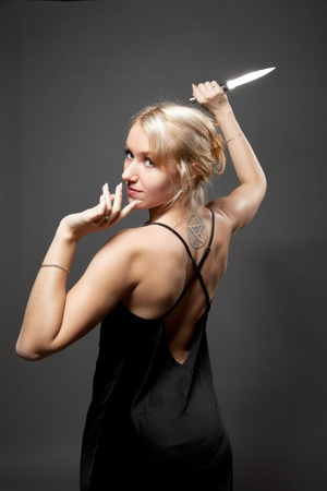 girl with knife: Beauty danger woman posing in evening dress with ritual knife