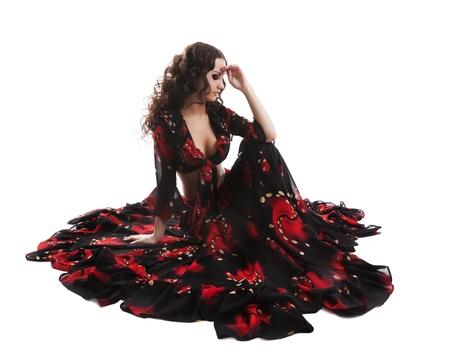 gitana: sentarse joven guapo en traje de gitana rojo y negro aislado