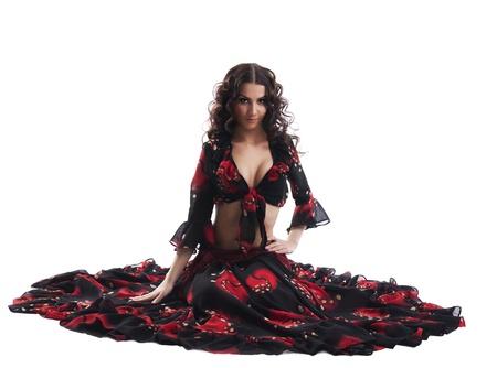 gitana: sentada, juventud, mujer linda en el flamenco rojo y negro traje aislado Foto de archivo