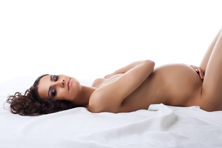Young sexy nude pregnant woman lay on white silk bed isolated Stock Photo - 12151623