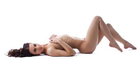 naked young women: Красивая молодая Обнаженная женщина лежала на белом Изолированные крупным груди Фото со стока