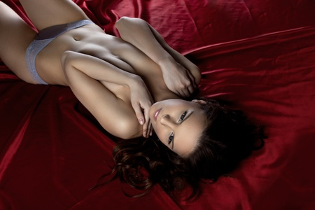nude fashion model: Young sexy woman lay on red silk - close breast with hands