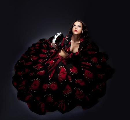 schattige jonge vrouw zitten in zigeuner zwart en rood kostuum geïsoleerd