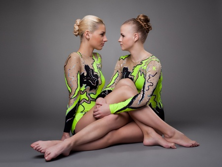 the gymnast: Young beauty acrobats sit on grey background - look unfriendly