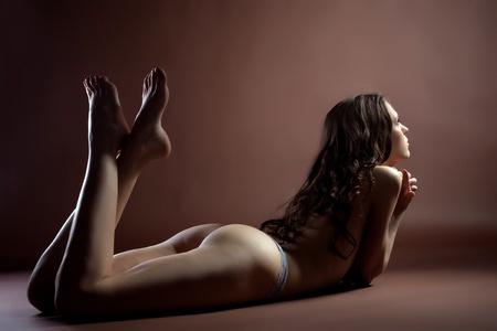 ragazza nuda: Bellezza donna sexy giaceva relax marrone - guardare la luce