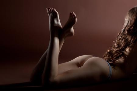 junge nackte m�dchen: Erstaunlich junge Frau posiert auf rotem in wei�en Dessous Lizenzfreie Bilder