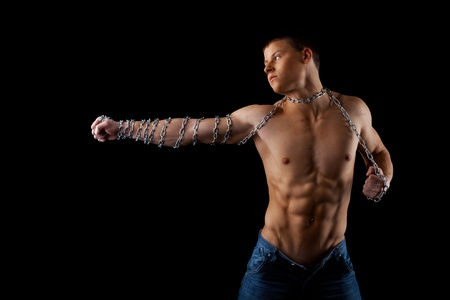 hand chain: aggressive athletic man with chain on hands fight on light