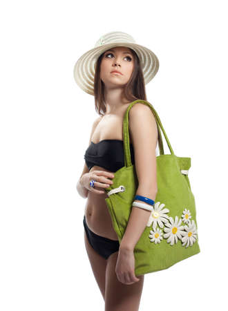 Young woman posing with beach bag and straw hat isolated photo