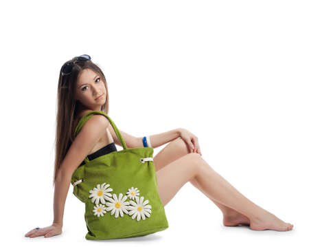 Yong woman sit with green beach bag with camomile flowers isolated  photo