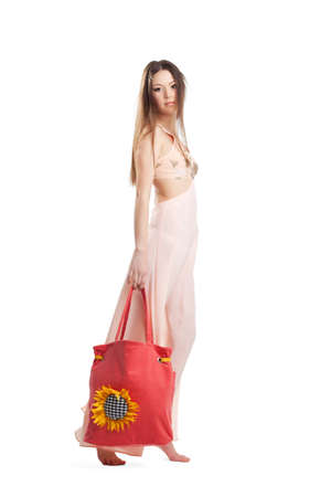 Beauty girl with long hair walk in rose dress and red beach bag isolated photo