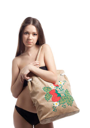 Young woman in black bikini posing with funny beach bag isolated photo