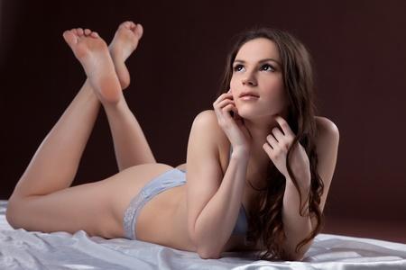 junge nackte m�dchen: Erstaunlich junge Frau posiert auf wei�er Seide in grau-BH Lizenzfreie Bilder