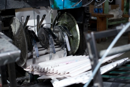 ready newspaper throw from production line in a print shop  photo