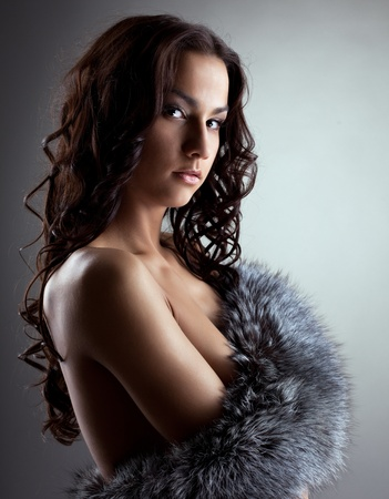 Amazing nude woman hiding breast by fur coat photo