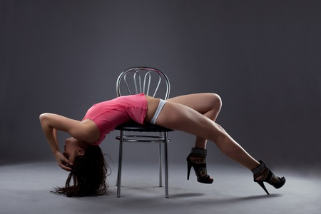 Beauty sexy go-go dancer posing in wet rose tank top on chair Stock Photo - 13168996