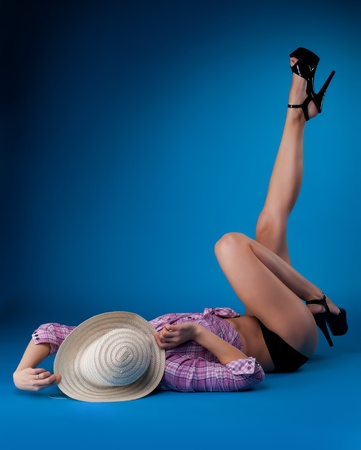 pin-up funny woman hide face by straw hat on blue background photo