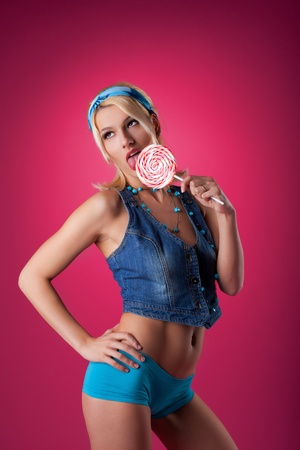 beauty blond jeans girl lick lollipop on pink background photo