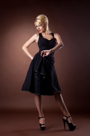 Cute woman in black pinup style dance on dark background photo