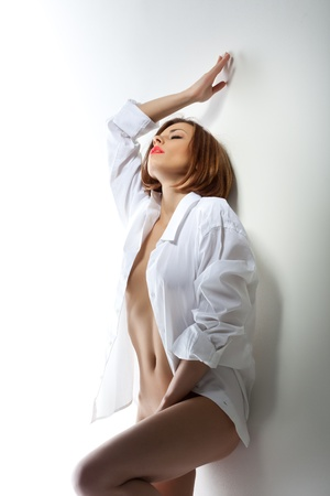Cute young woman touch herself with pleasure in white shirt stand near a wall