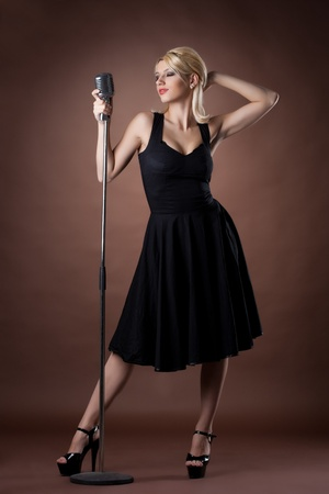 microphone retro: Beauty singer - woman pin-up portrait in black with microphone Stock Photo