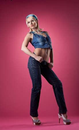 Tall sexy girl posing in jeans on pink background photo