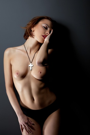 naked breast: sexy young woman with cross on naked breast near dark wall