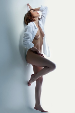 Beautiful naked woman in shirt erotic portrait near white wall Stock Photo - 13041473