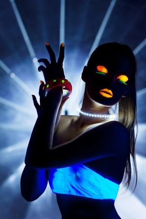 Chica con la danza ultravioleta discoteca de maquillaje en la oscuridad