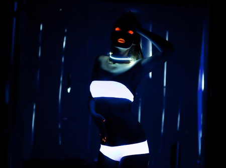 UV-light and special glow make-up on girl dance in dark photo