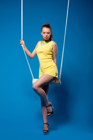 Sexy woman in yellow on swing with glow make-up Stock Photo - 13125460