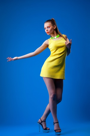 Young sexy woman in yellow cloth on blue and bright make-up Stock Photo - 13125454