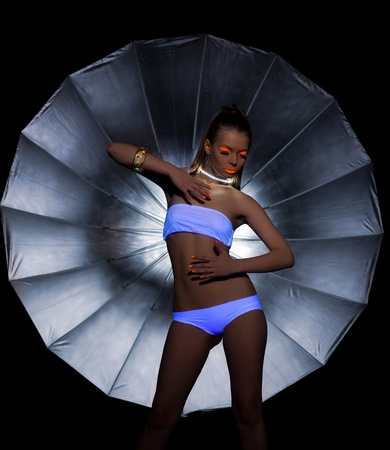 bodypaint: Sexy Girl dance with ultraviolet glow make-up and silver umbrella on background
