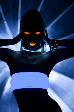 neon background: Girl with ultraviolet make-up disco dance in dark