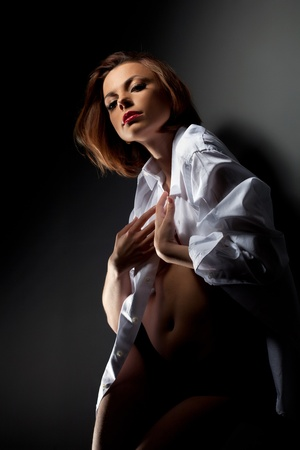 erotic nude women: Desired sexy young woman in white shirt near dark wall