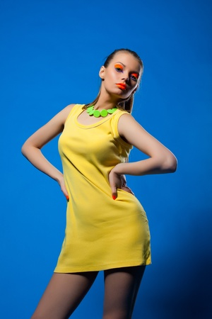 Young sexy woman in yellow cloth on blue and bright make-up Stock Photo - 13152128