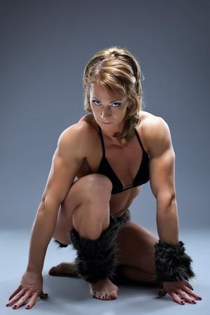 Aggressive female body builder posing in amazon fur costume photo