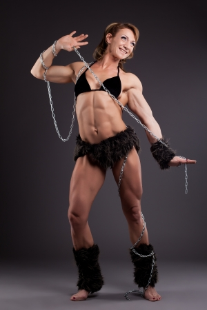 sexual anatomy: Strong athletic woman body builder posing in amazon fur costume with chain Stock Photo