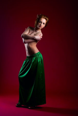 Beauty woman posing on red in green dress - hide breast by hands Stock Photo - 13248073