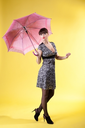 sexy woman posing with rose umbrella pin-up style on yellow Stock Photo - 13825320