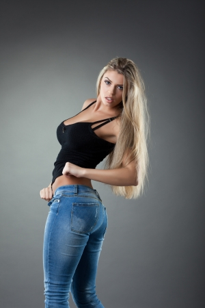 Studio portrait of sexy blonde young wonan in jeans photo