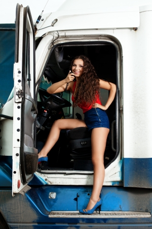 Brunette young woman posing in truck cabin